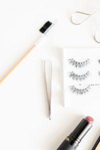 makeup flat lay eyelashes tweezers lipstick eyelash curler
